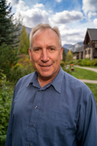 Portrait of Ross Jansen of Spring Creek Real Estate in Canmore, wearing a blue collared shirt, and standing and smiling in front of green foliage with mountains in the background.